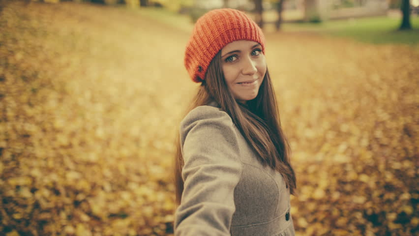 Young woman pulling her boyfriend through autumn park with leafs pov