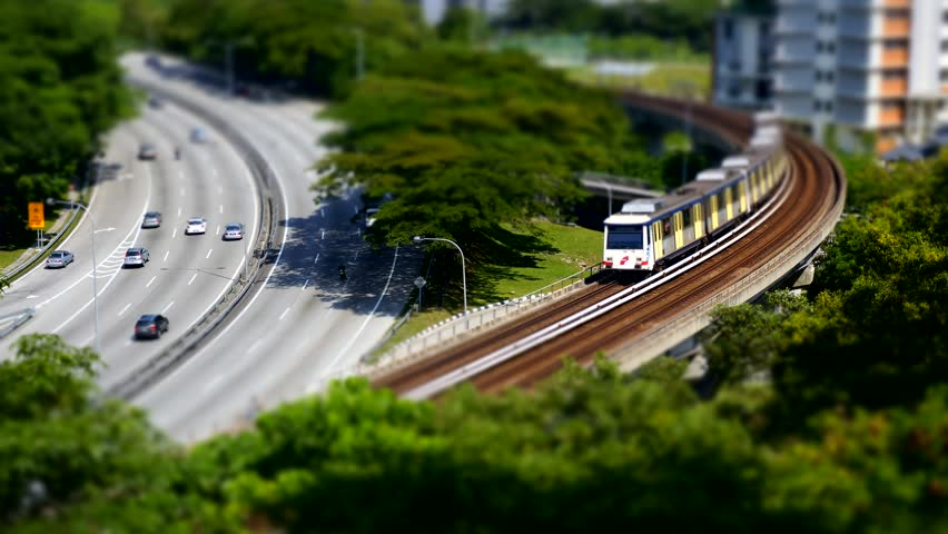 Aerial view - cars and light rail train miniature tilt shift lens effect time lapse.