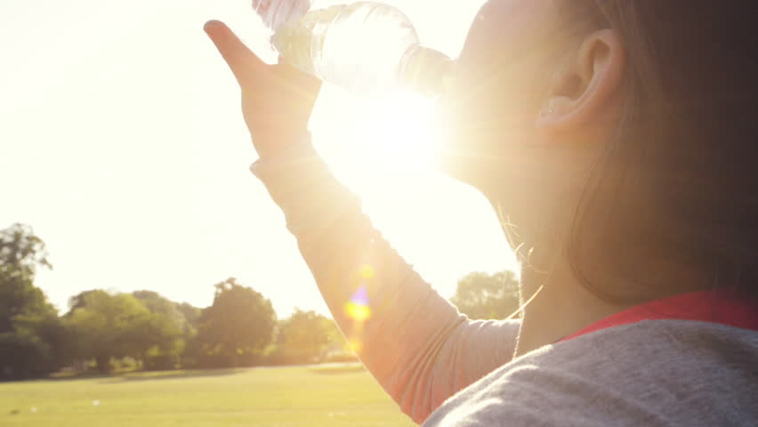 Fitness woman drinking water outdoors in park