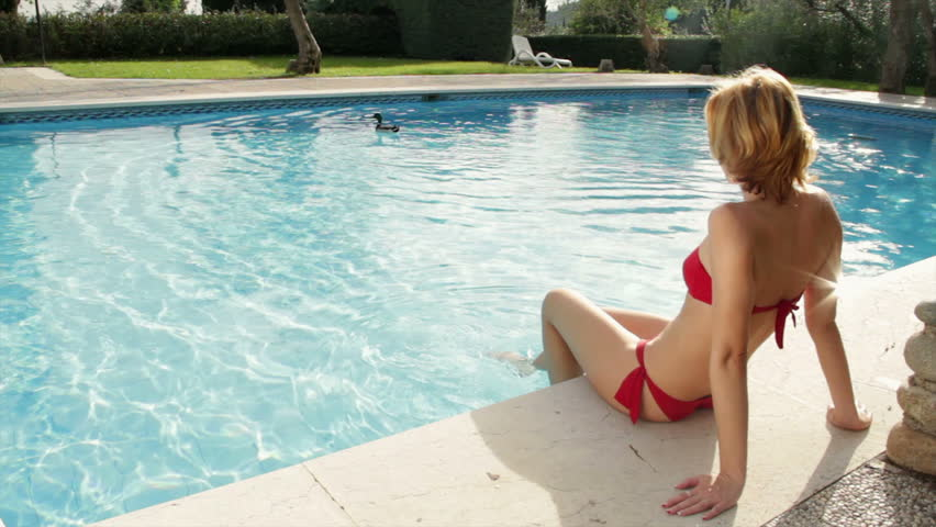 Woman in red bikini sitting by the swimming pool and enjoying the summer sun high definition - Define poolside ...
