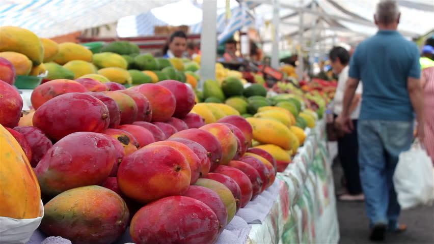 A street market in sao paulo brazil with people buying fresh fruits. selective focus.