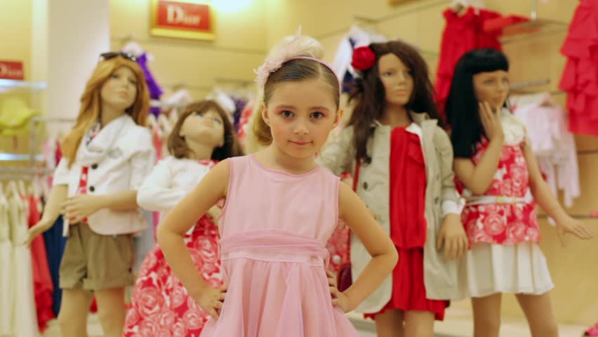beautiful girl in a pink dress posing to the camera on the background of the dummies