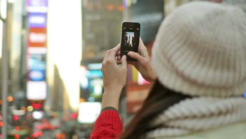 Tourist Snaps Picture in Times Square - Beautiful Pretty Girl Takes Photo with Smartphone in Busy, Crowded, Cold Manhattan, New York City Winter and Smiles at Camera