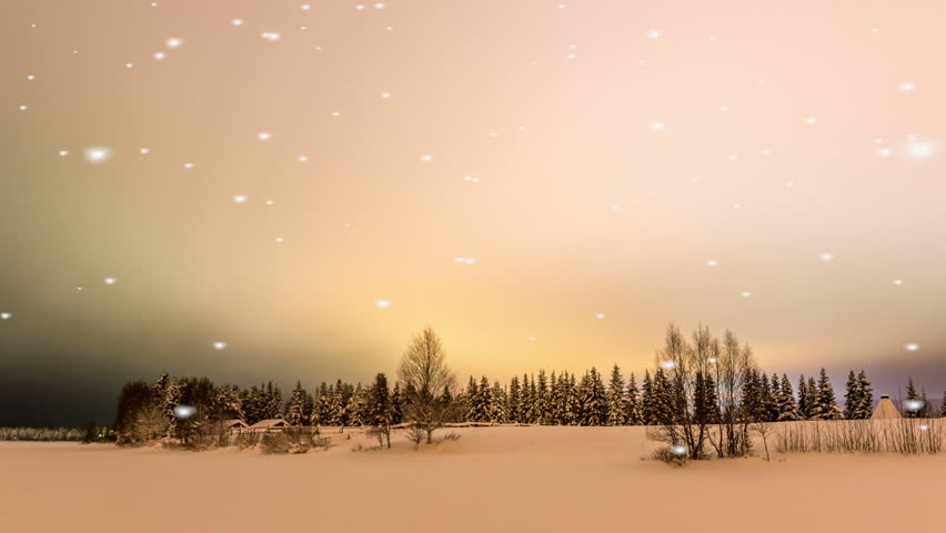 Beautiful glowing orange sunset or sunrise over a tranquil winter wonderland with falling snowflakes on forest trees