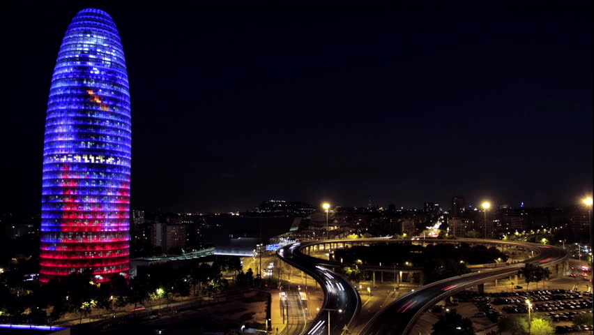 BARCELONA, SPAIN - AUGUST 29, 2013:  Timelapse of The Torre Agbar iconic cone shaped building lit up at night with highway and speed cars, Barcelona, Spain. AUGUST 29 2013: (Time Lapse AGBAR tower)