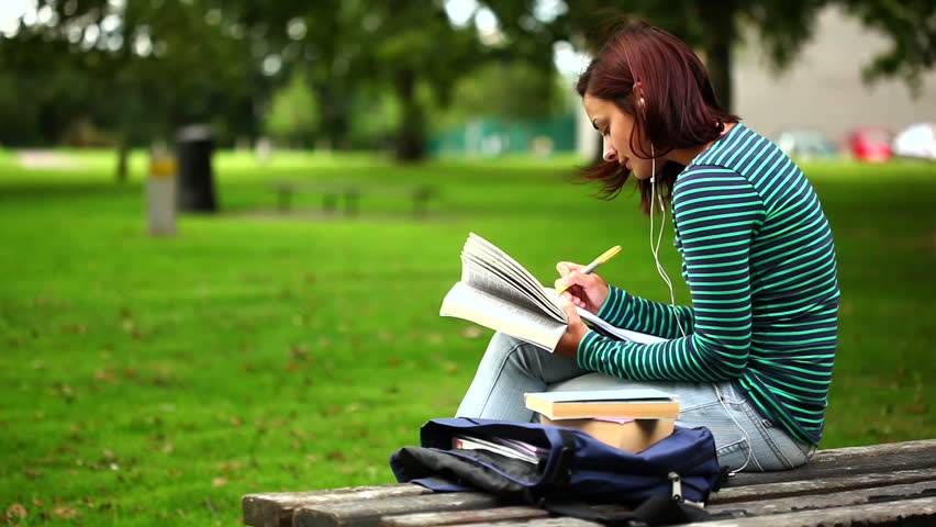Pretty student sitting on bench reading a book listening to music at the university