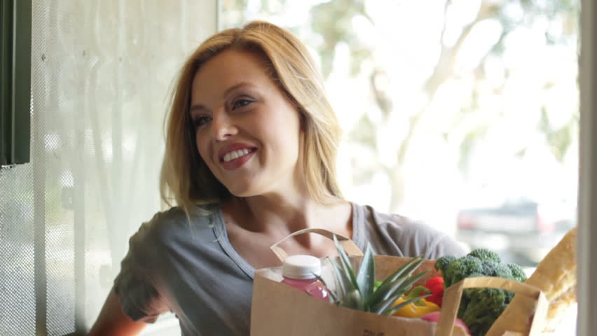 Door opens to reveal an attractive young blonde woman delivering groceries to a