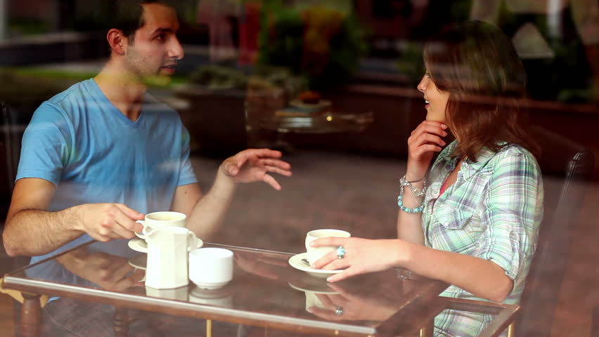 Student couple chatting together in the canteen having coffee in college