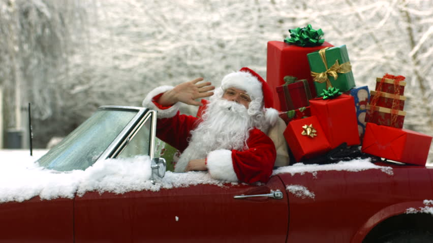 Santa Claus waving from convertible car full of gifts