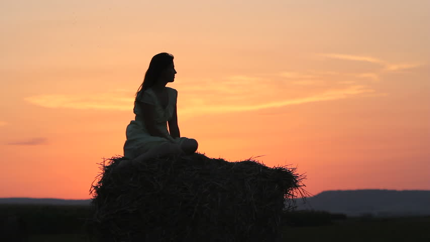 Dream girl, beautiful lady silhouette on straw stack at sunset, charming sky, natural little mermaid