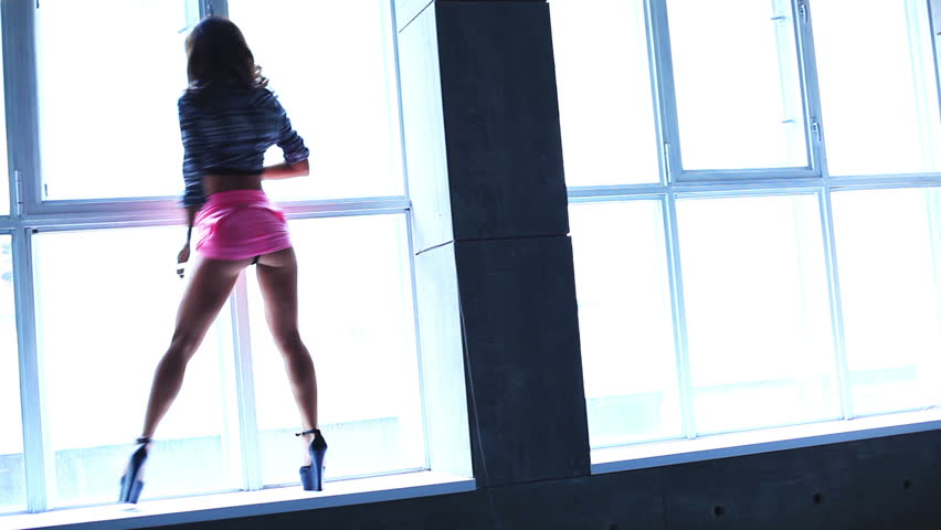 Young woman dancing on window background.