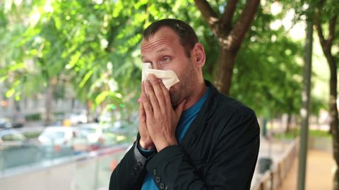 Sick man blowing his nose in the tissue standing in the city