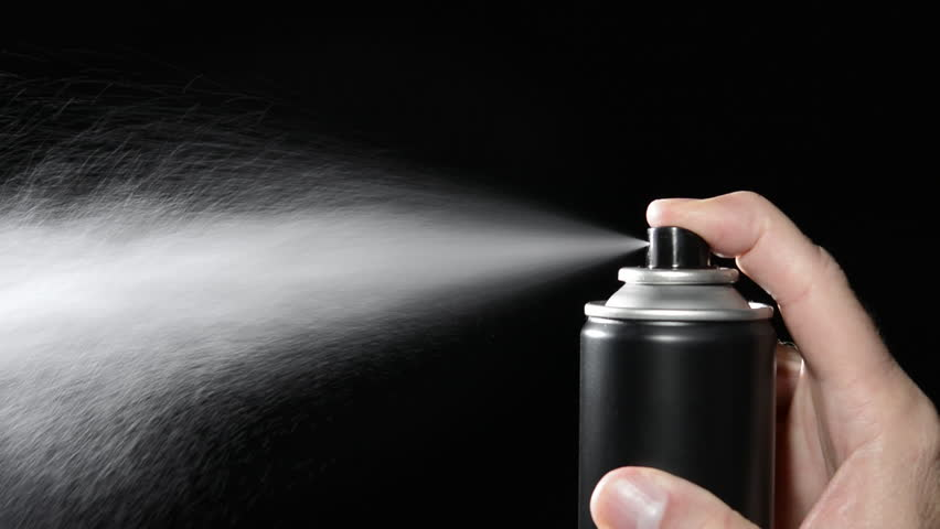 A man depresses the trigger on an aerosol spray can.