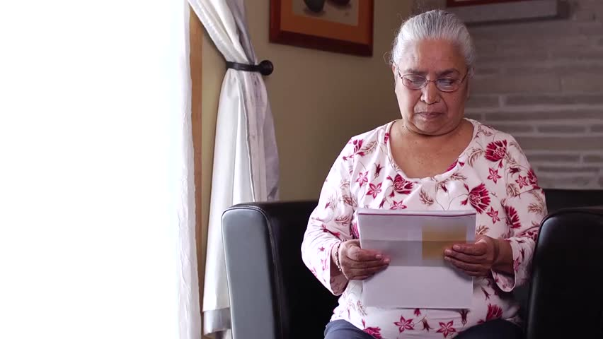 Senior latin woman reading her household bills and can't understand what she is looking at.