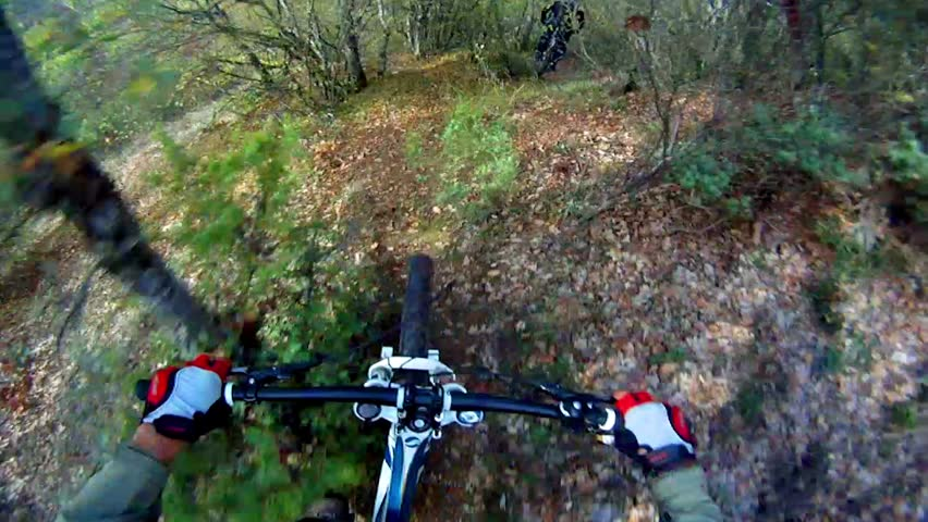 Extreme Mountain Bike race. View from handlebars of man on bike on dirt track pov