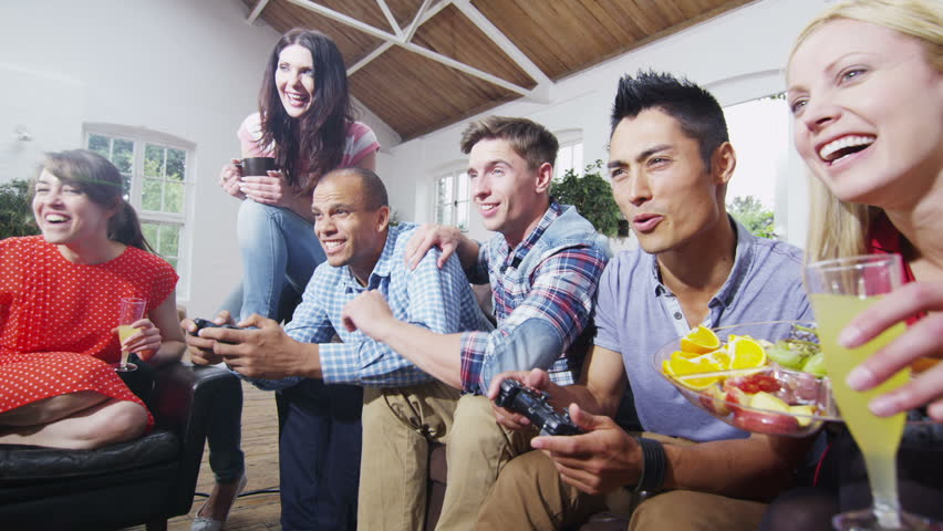 Happy mixed ethnicity group of friends socializing at home and playing video games. In slow motion.