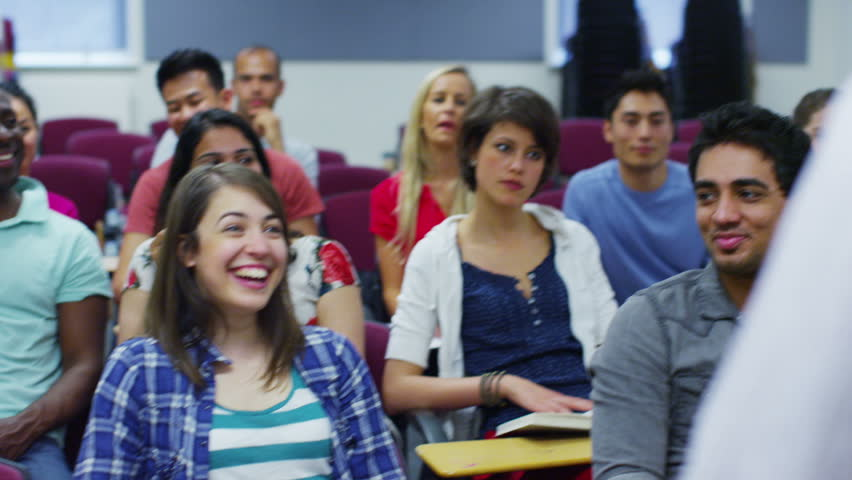 Cheerful mixed ethnicity group of students in a classroom, listening as their teacher holds a lecture. In slow motion.