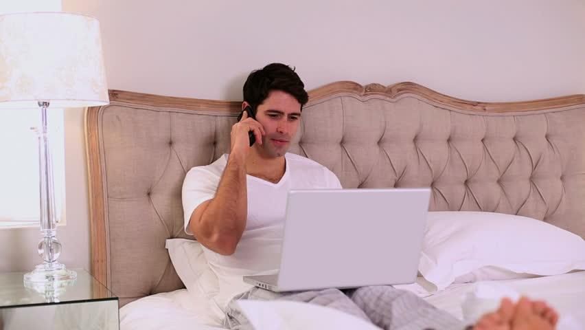 Happy handsome man working in bed in bright bedroom