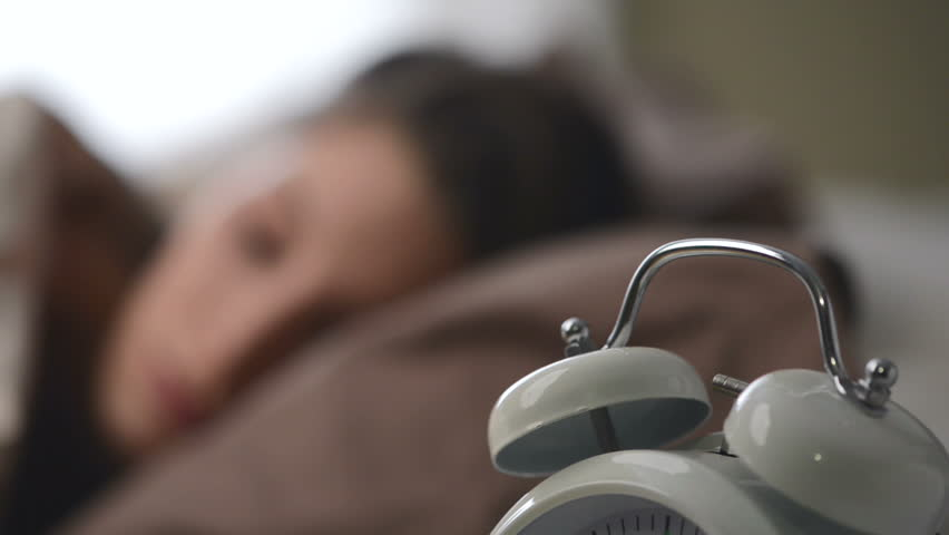 A young woman is woken by her alarm clock