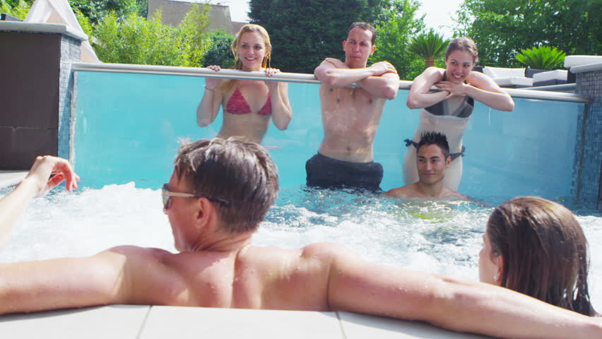 Happy group of young friends enjoying a pool party at swimming pool with clear glass panel and hot tub. In slow motion.
