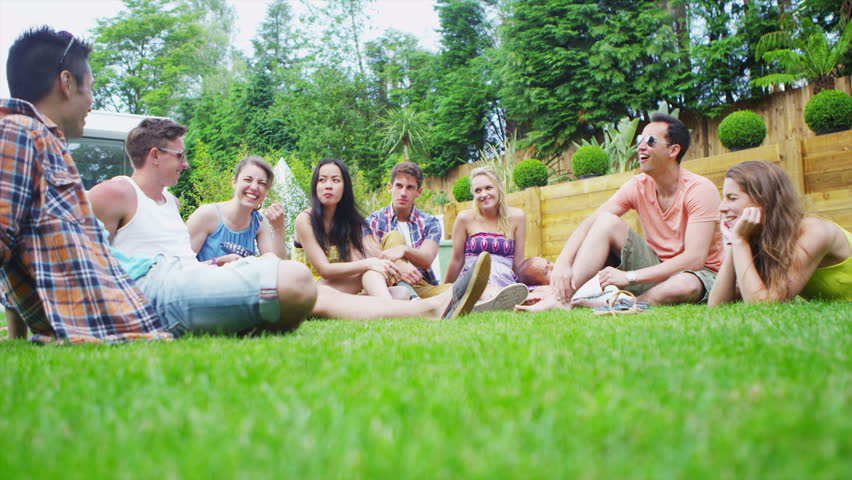 Cheerful group of young friends relaxing outdoors and chatting together on a summer day.