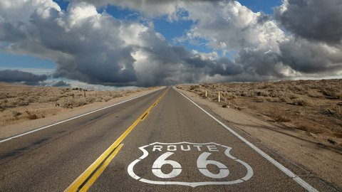 Route 66 highway pavement sign with time lapse clouds.