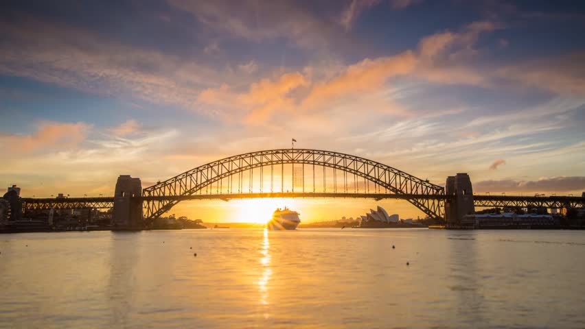 SYDNEY - AUSTRALIA - NOVEMBER 20: (Timelapse) A beautiful sun rises over Sydney Harbour revealing the Bridge and Opera House welcoming new visitors as a large cruise ship enters on Novermber 20, 2013.