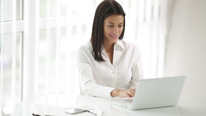 Charming young woman sitting at office desk using laptop looking at camera and