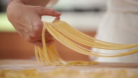 Adult woman hands preparing dough for homemade pasta.