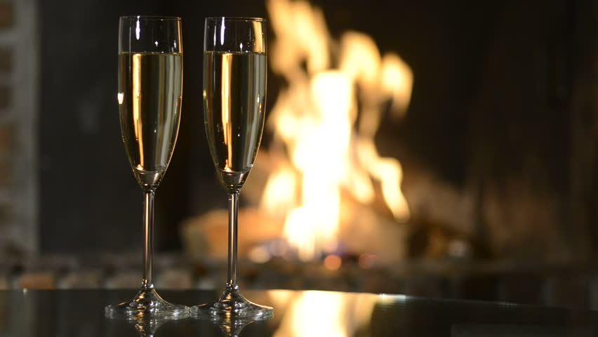 Two champagne glasses in front of fireplace  | Shutterstock HD Video #5190401