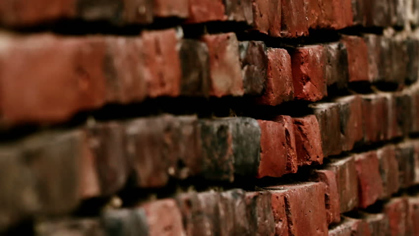 Side way image of the brick wall being shown. The brick wall is mostly red brown in color.