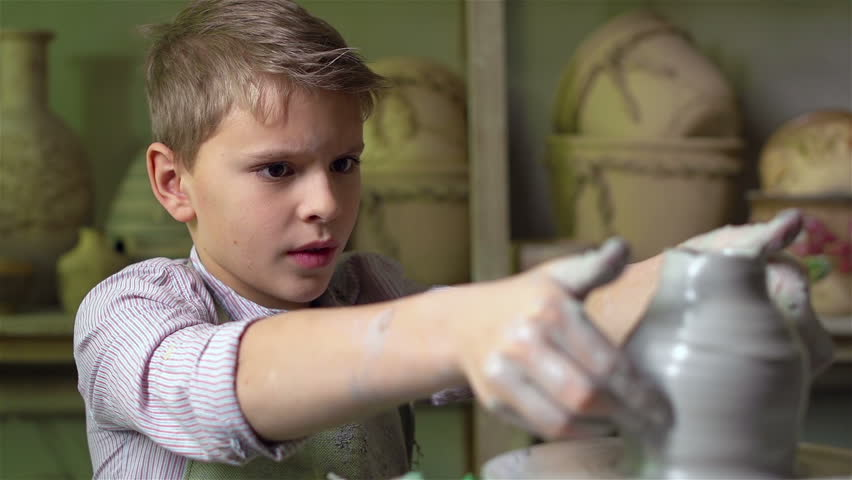 Serious lad being concentrated on making a clay ware on a pottery wheel