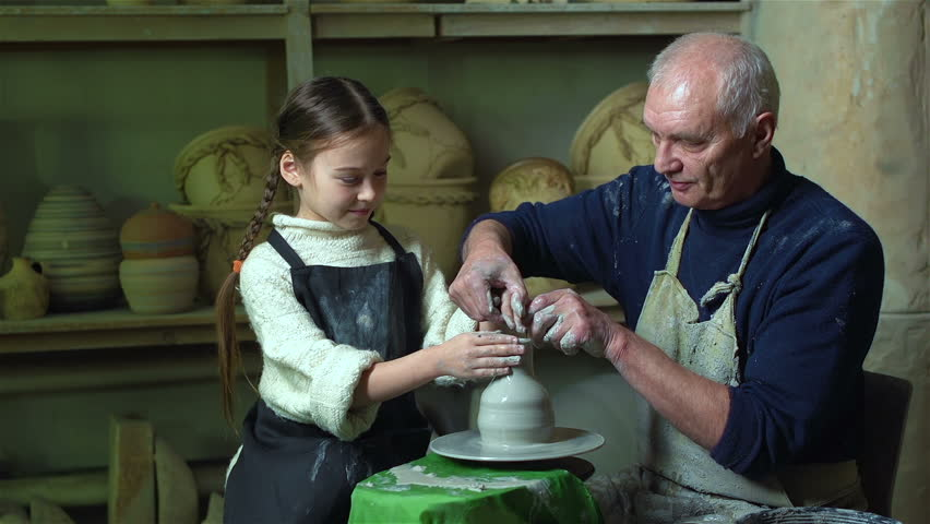 Grandfather giving the basics of pottery to his cute granddaughter