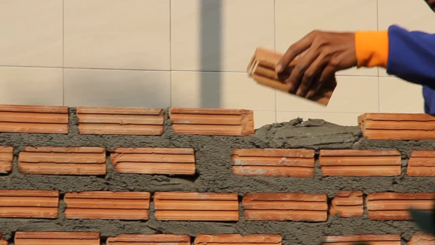 Worker build brick wall with trowel, closeup view at construction site