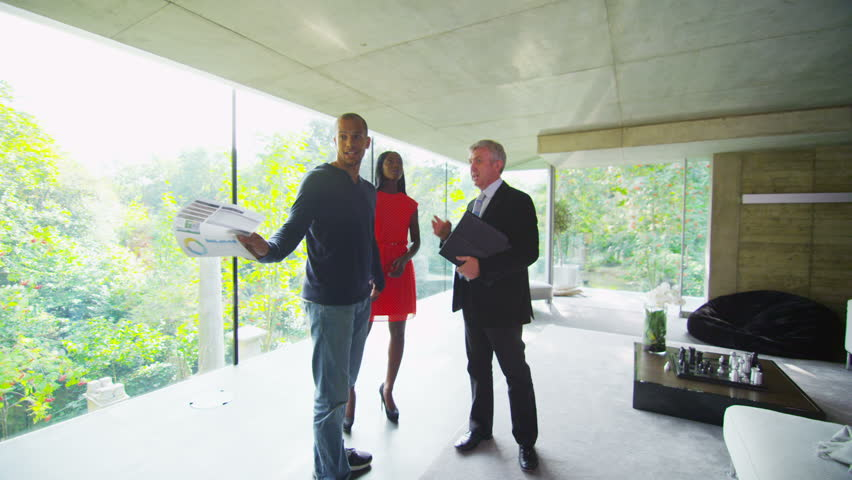 Young couple being shown round a luxury modern home by the estate agent