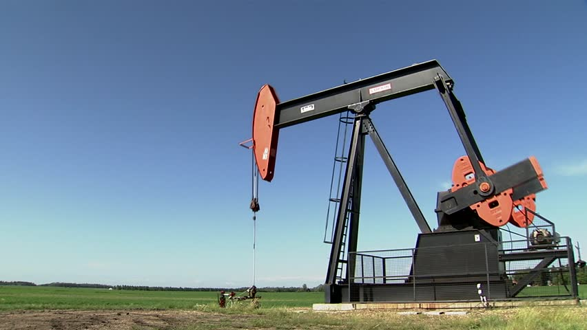 Oil rig pumping in Albertan countryside. (Pan Right)