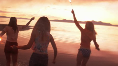 Teenage Girls With Sparklers On The Beach At Sunset
