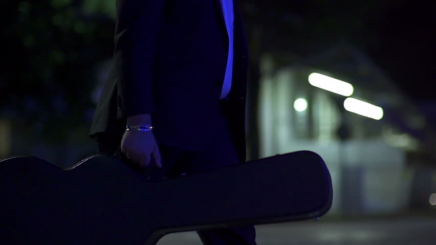 Man carrying a guitar in the dark night in slow motion