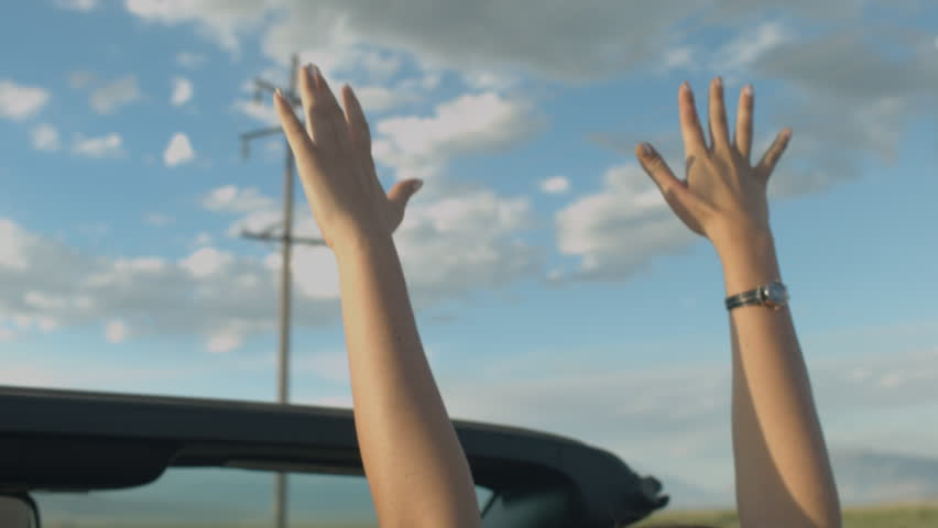 Teen Girl In A Convertible Raises Hands In The Breeze Against A Sunny Cloudscape