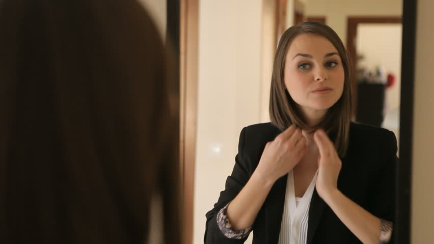 Confident woman gets ready in front of a mirror, looking at herself happy. She smiles and leaves.