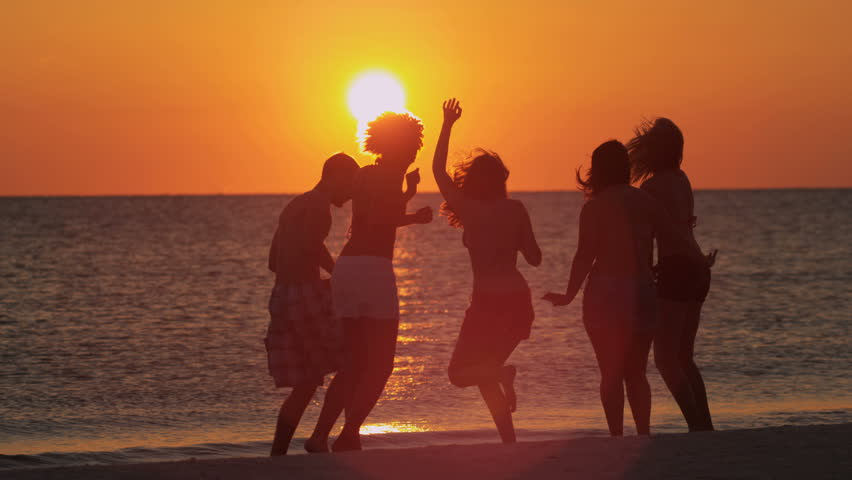 Happy male female college friends laughing dancing on beach at sunset on weekend break shot on RED EPIC, 4K, UHD, Ultra HD resolution