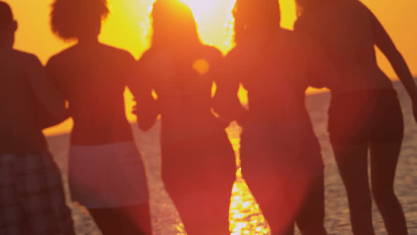 Male female young friends enjoying freedom college break coastal beach watching sunset together shot on RED EPIC, 4K, UHD, Ultra HD resolution | Shutterstock HD Video #5315543