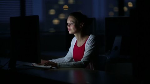 Young female student working alone in a computer classroom, late at night