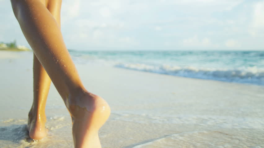 Legs only young ethnic girl walking barefoot along wet sand beach beside tropical ocean shot on RED EPIC, 4K, UHD, Ultra HD resolution
