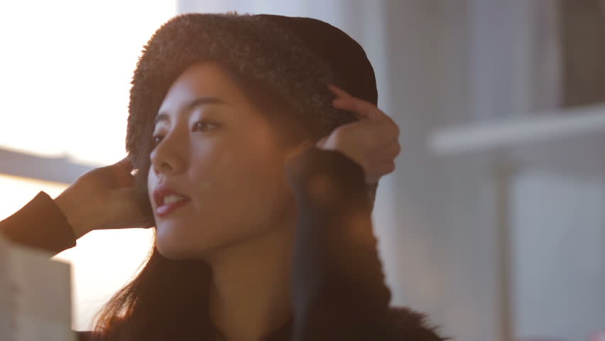 Close up clip, with natural sunlight flare, of a beautiful asian woman taking her newly bought hat from a shopping bag & trying it on.