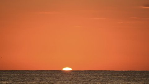 Ocean sunrise in clear sky time lapse zoom for big sun HD 1080. A beautiful ocean sunrise time lapse in clear, cloud-less skies. Zoomed in for a large sun.