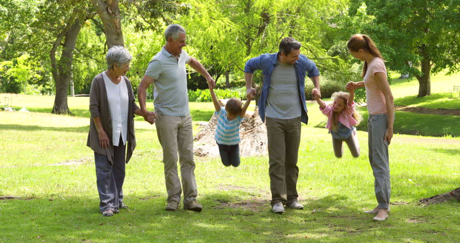 Multi generation family smiling and holding hands in a park on a sunny day
