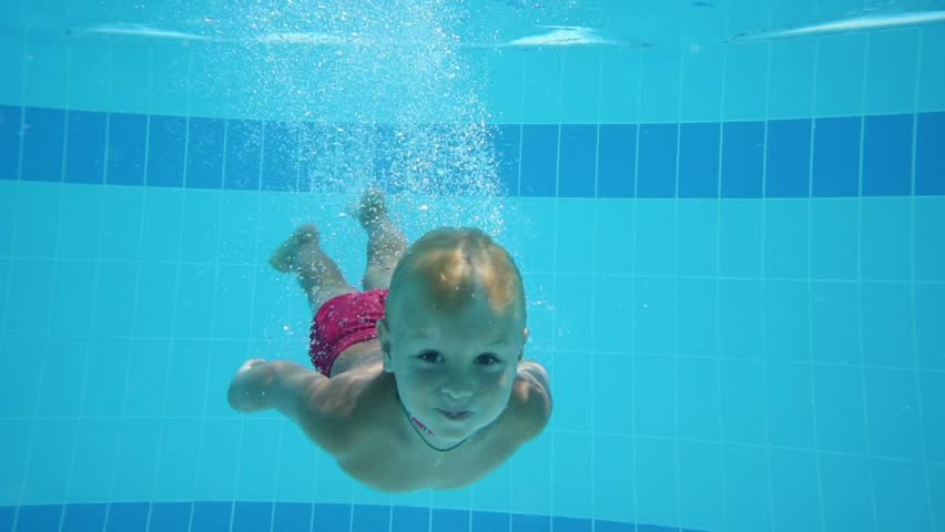 Cute little boy dives in blue pool with open eyes and floated back