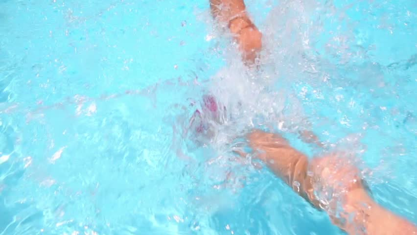 Little boy in red trunks dive into water from edge of the pool