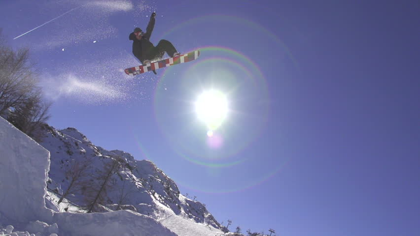 SLOW MOTION: Snowboarder jumping over the sun #5420501